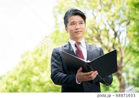 新緑の屋外で資料を見るビジネスマン 68871633