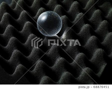 黒の立体的な波模様の上に透明な球体 68876451