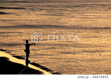 夕暮れ時のオレンジ色に染まる海で釣りを楽しむ男性 68878848