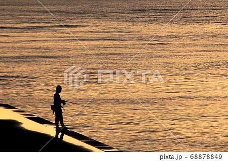 夕暮れ時のオレンジ色に染まる海で釣りを楽しむ男性 68878849