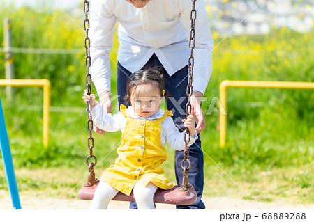 ブランコでパパ・ママと遊ぶかわいい女の子 68889288