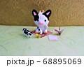金色の背景の前に座るミニチュア粘土の牛と折り鶴と葉書 68895069