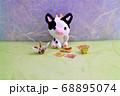 座るミニチュア粘土細工の牛と折り鶴 68895074