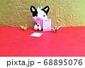 金色の背景の前に座るミニチュア粘土の牛と折り鶴と葉書 68895076