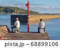 釣りを楽しむ男性二人  防波堤に腰掛けて釣りをする二人の男性 68899106