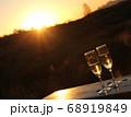 夕日に照らされ黄金色に輝く二対のシャンパングラス 68919849