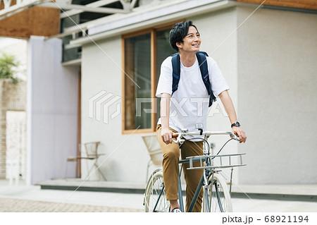 自転車に乗って出かける男性 68921194