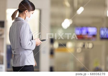 マスク姿で改札で待ち合わせをする女性 68936270
