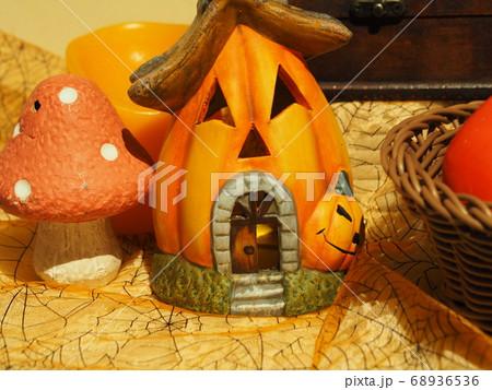 ハロウィンの笑っているカボチャの家と白ドットのあるオレンジ色のキノコの置物 68936536