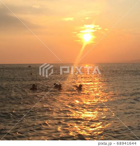 太陽柱と夕日が当たる海の中で泳ぐ人々 68941644
