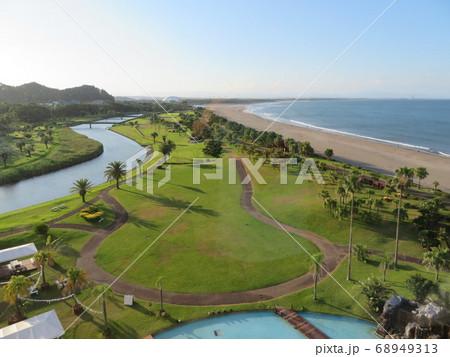 早朝にリゾートホテル客室から眺める風景(海と砂浜と緑の芝生の曲線美) 68949313