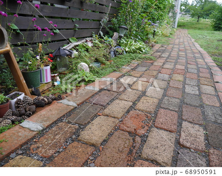季節の花や植物で彩られたレンガのアプローチ 68950591