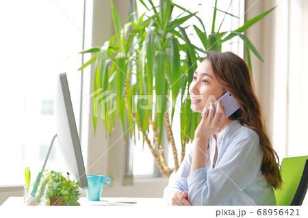 柔らかな笑顔で電話するビジネスウーマン 68956421