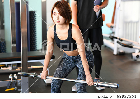 デッドリフトをする若い女性とトレーナー 68957501