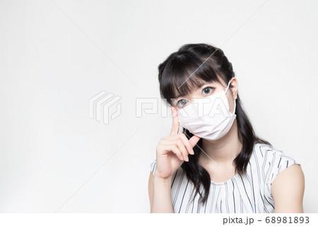 オフィスカジュアルな服装とマスク姿で考えている女性 68981893
