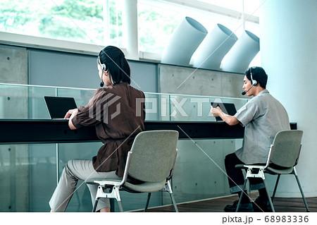 ソーシャルディスタンスをとってオフィスでチャットするカジュアル衣装の若い男女オペレーター 68983336