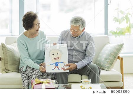 似顔絵を持って笑顔のシニア夫婦 69002890