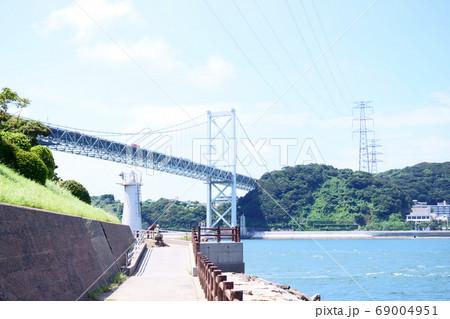 関門海峡を跨ぐ関門大橋と海の安全を守る門司埼灯台 69004951