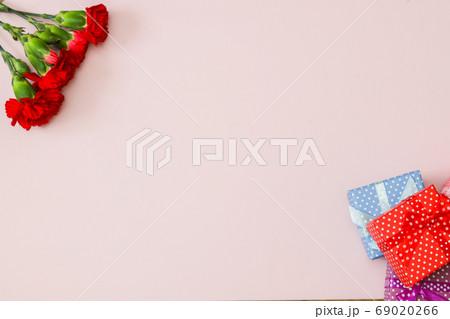 ピンク背景のカーネーションとギフトボックス 69020266