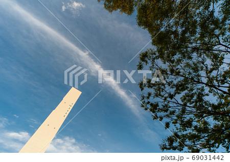 白い塔とカーブする雲と樹木と青空 69031442