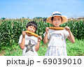 トウモロコシ畑で焼とうもろこしを食べる子供 69039010