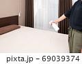 寝室のベットに消臭スプレーをする女性 69039374