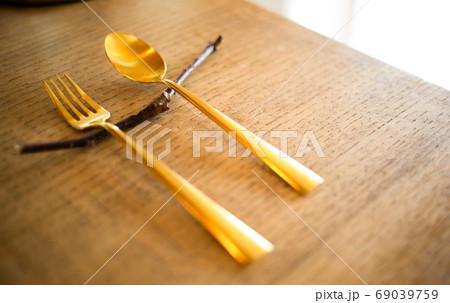 テーブルに並べた金色のフォークとスプーン 69039759
