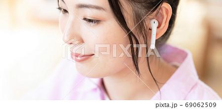 ワイヤレスイヤホンをする笑顔の若い女性の顔のアップ バナーサイズ 69062509