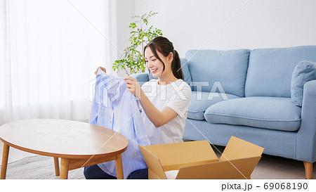 通販の商品が届き喜ぶ笑顔の若い女性 69068190