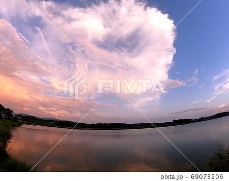 夕方、湖の上に発達し明るい色づく大きな雲 69073206