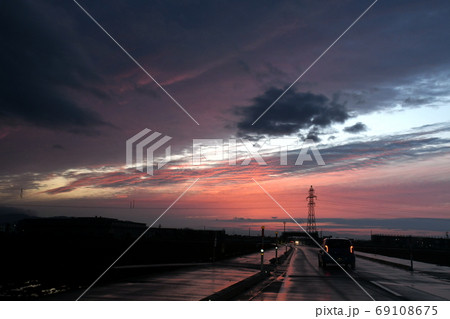 雨上がり、夕焼け雲に向かって走る道 69108675