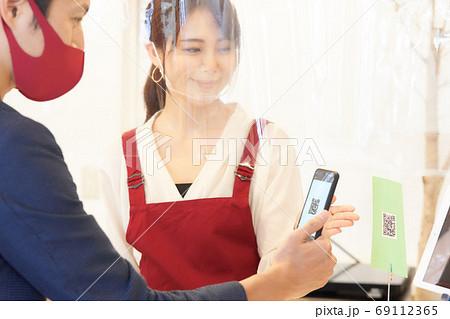 感染症対策をした店でQRコードを案内する店員と読み取るお客 69112365