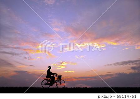 夕陽を背景に自転車通学する男子高校生のシルエット 69114761