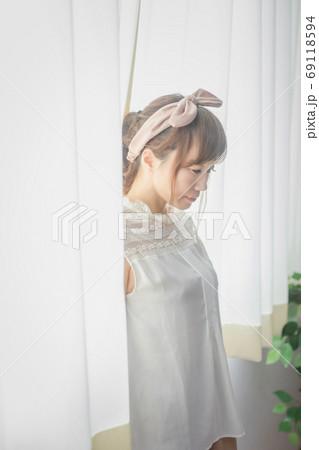 自然光が入る朝の窓辺に佇む若い女性 69118594