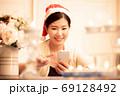 クリスマスのイメージ スマホを使うサンタ帽の女性 69128492
