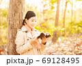 秋の自然の中で本を読む女性 69128495