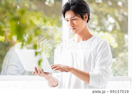 ノートパソコンを手に窓辺に立つ若い男性 69137019
