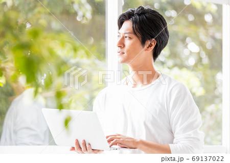 ノートパソコンを手に窓辺に立つ若い男性 69137022