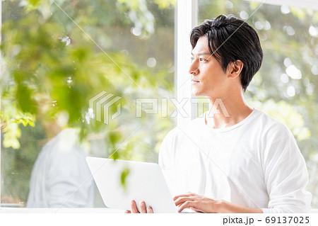 ノートパソコンを手に窓辺に立つ若い男性 69137025