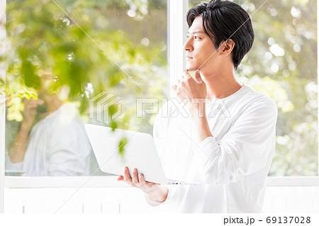 ノートパソコンを手に窓辺に立つ若い男性 69137028