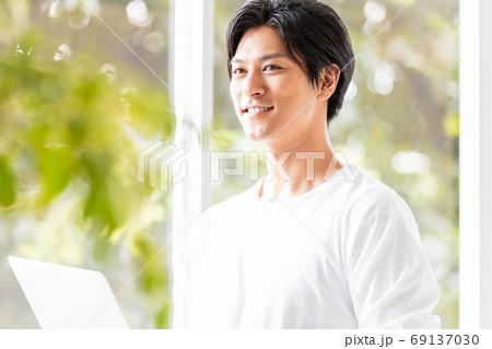 ノートパソコンを手に窓辺に立つ若い男性 69137030