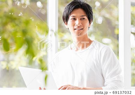 ノートパソコンを手に窓辺に立つ若い男性 69137032