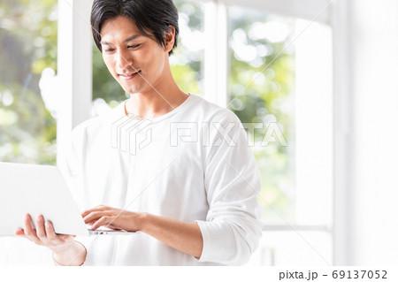 ノートパソコンを手に窓辺に立つ若い男性 69137052