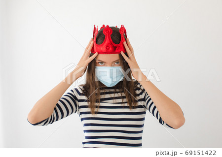Young woman in medical mask and crown 69151422