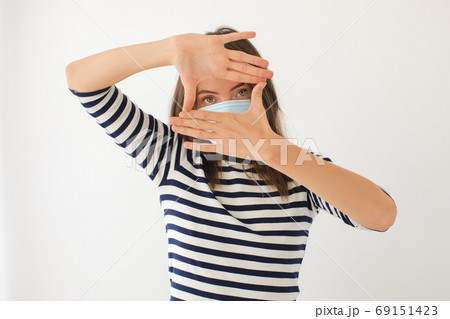Young woman in medical mask making frame with hands 69151423