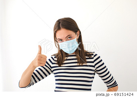 Caucasian young woman with face mask showing thumb up 69151424