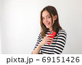 Smiling woman surfing smartphone at home 69151426