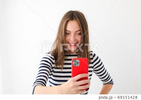 Smiling woman surfing smartphone at home 69151428
