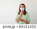 Shocked woman in mask using smartphone 69151432