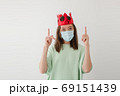Woman in mask and crown pointing up 69151439